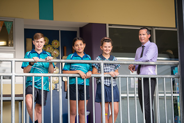 students and principal leaning on railing